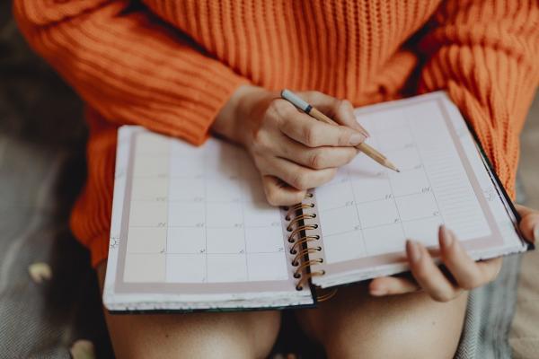 カレンダーに予定を書く女性