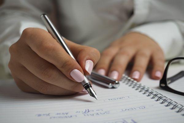 女性がボールペンでノートに記入している