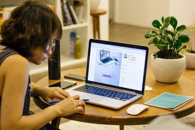 机とPCに向かう女性の写真